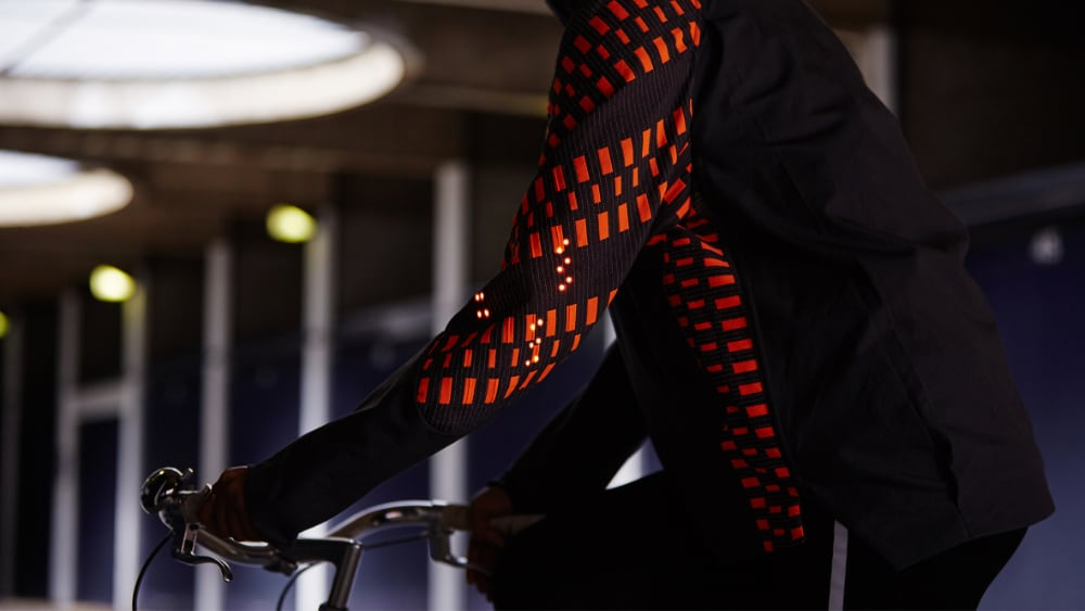 Photo of cyclist wearing a cycling Jacket incorporating electronic yarn with lit LEDs on the elbow